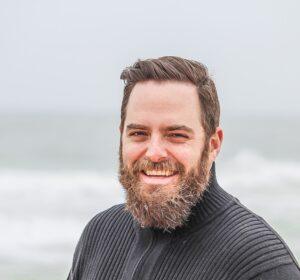 Mand ser glad ud og står ved havet