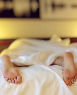 Person sover i sin seng med fødderne der stikker ud