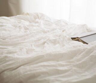 Seng med hvidt sengebetræk over