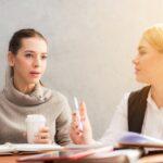 To damer sidder og taler til møde